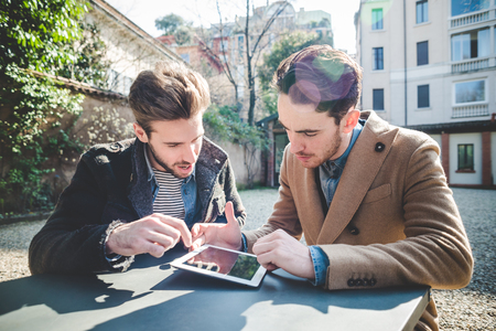 two young handsome fashion model businessmen using tablet  outdoors photo