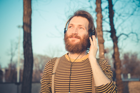 young bearded stylish handsome hipster man listening music with headphones outdoors photo