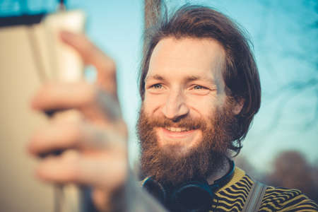 young bearded stylish handsome hipster man using tablet outdoors photo
