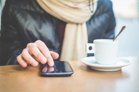 スマート フォンとバーでコーヒーを 1 杯で女性の手のクローズ アップ 写真素材