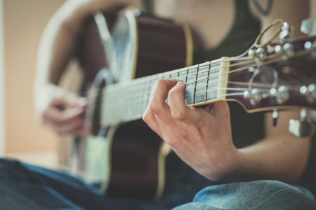 close up of woman hands playing guitar at home photo