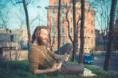 young bearded stylish handsome hipster man using tablet outdoors Stock Photo - 29040849