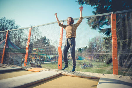 young bearded stylish handsome hipster man jumping on trampoline at playground  photo