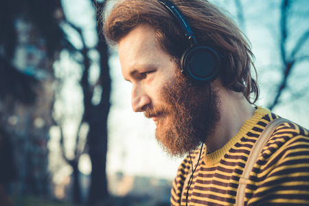 young bearded stylish handsome hipster man listening music with headphones outdoors Stock Photo - 29040851