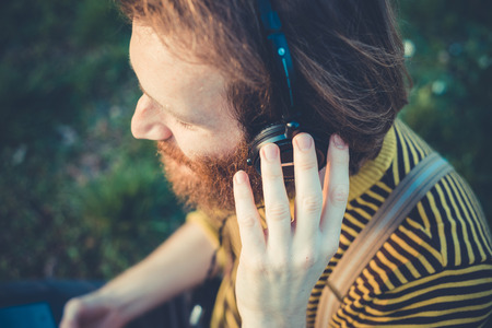 young bearded stylish handsome hipster man listening music with headphones outdoors Stock Photo - 29040852