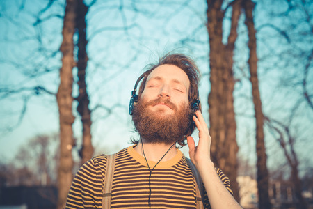 young bearded stylish handsome hipster man listening music with headphones outdoors Stock Photo - 29040853