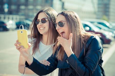 都市の selfie のスマート フォンを使用して 2 つの美しい若い女性
