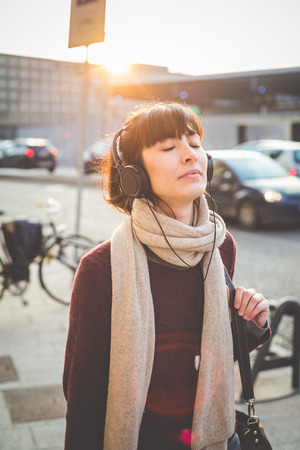 young beautiful hipster woman listening music with headphones in the city photo