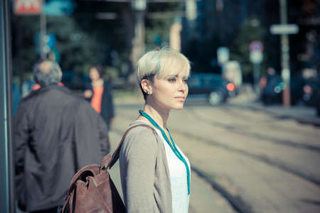 pendular: beautiful young blonde short hair hipster woman in the city