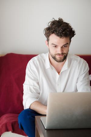 trabajando en casa: apuesto inconformista hombre moderno dise�ador que trabaja en casa usando la computadora port�til en casa