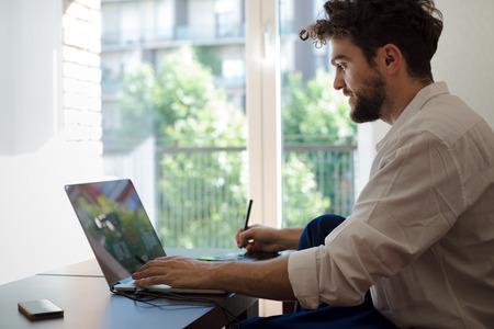ハンサムな流行に敏感な現代人デザイナーの作業ホーム自宅でラップトップを使用して