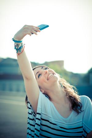 mooie brunette: jonge mooie brunette vrouw selfie met slimme telefoon in de stad Stockfoto