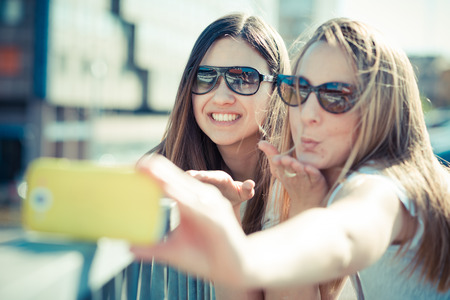 two beautiful young women using smart phone for selfie in the city photo