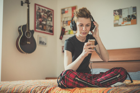 young lesbian stylish hair style woman listening to music at home
