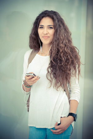 beautiful curly long brunette hair moroccan woman using smart phone in the city photo