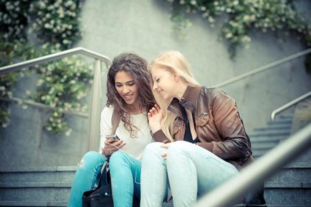 도시에서 스마트 폰을 사용하는 금발 머리와 갈색 머리 아름다운 세련된 젊은 여성