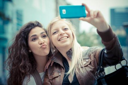금발 머리와 갈색 머리 아름다운 세련된 젊은 여성들은 도시에서 selfie