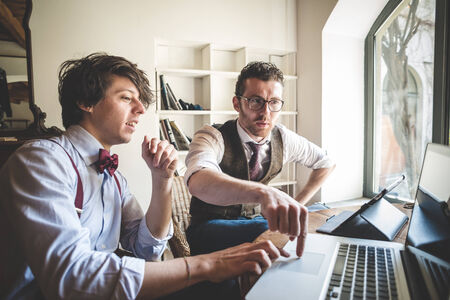 two young hipster stylish elegant men working with notebook and tablet at home  photo