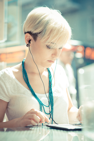 beautiful young blonde short hair hipster woman at the cafe photo