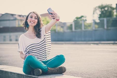 市内のスマート フォンと若い美しいブルネットの女性 selfie