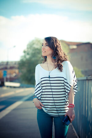 young beautiful brunette woman with smart phone listening music  in the city photo
