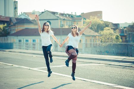 two beautiful young women jumping and dancing in the city photo