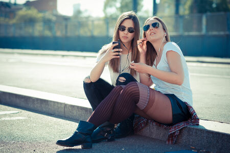 two beautiful young women using smart phone in the city photo