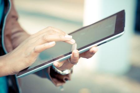 Sluit omhoog van Afrikaanse vrouwenhanden gebruikend tablet