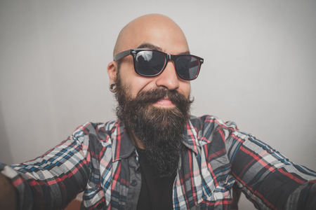 hipster long bearded and mustache man with shirt squares selfie
