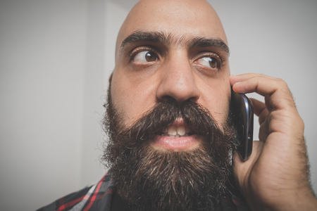 hipster long bearded and mustache man with shirt squares calling with cellphone photo