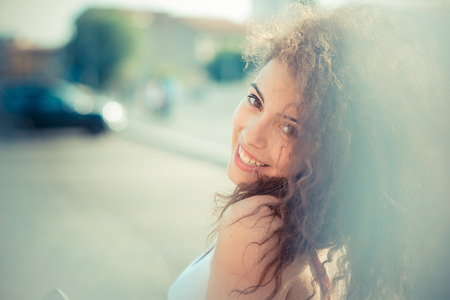 young beautiful long curly hair hipster woman in the city photo