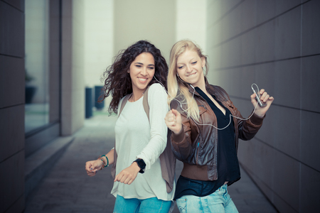 blonde and brunette beautiful stylish young women in the city photo