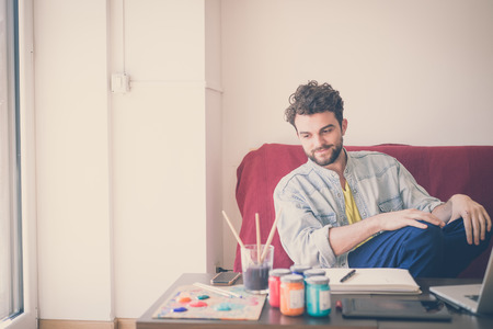 man painting: handsome hipster modern man painting at home