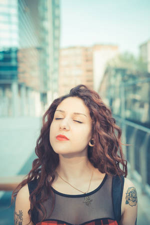 young beautiful hipster woman with red curly hair in the city photo
