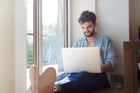 handheld computer: handsome hipster modern man designer working home using laptop at home