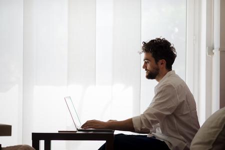 Bello pantaloni a vita bassa uomo moderno designer che lavorano a casa utilizzando il computer portatile a casa Archivio Fotografico - 31665205