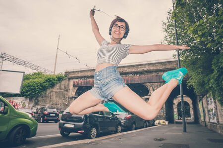 young hipster woman listening to music jumping in the city photo