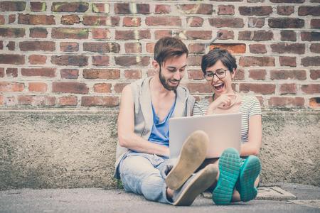 친구의 커플 젊은 남자와 여자 도시에서 노트북을 사용