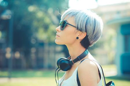 街でヘッドフォンの音楽を持つ若い美しい短い青髪流行に敏感な女性
