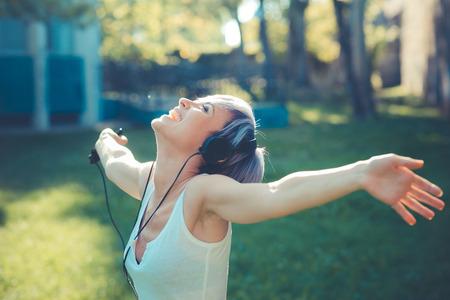ヘッドフォンの音楽都市で若い美しい短い青髪流行に敏感な女性 写真素材 - 31657418