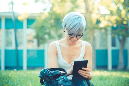 young beautiful short blue hair hipster woman using tablet device in the city photo