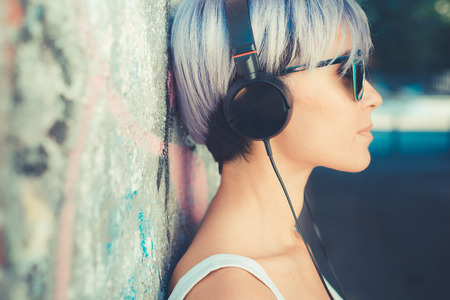 young beautiful short blue hair hipster woman with headphones music in the city