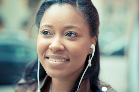 beautiful african young woman listening music earphones in the city photo