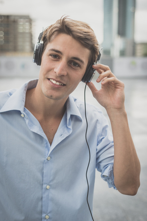 young model hansome blonde man with music headphones in the city Stock Photo