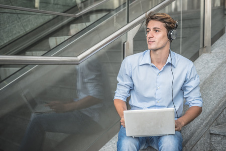 hansome: young model hansome blonde man with notebook smartphone and headphones in the city Stock Photo