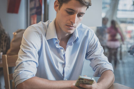 hansome: young model hansome blonde man using smartphone at the bar Stock Photo