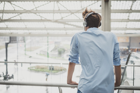 young model hansome blonde man with headphones in the city Stock Photo