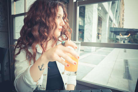 young beautiful hipster woman with red curly hair at the bar photo