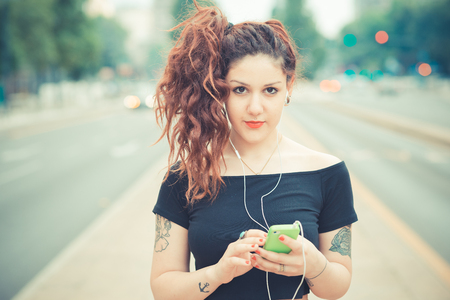 young beautiful hipster woman with red curly hair listening music in the city photo