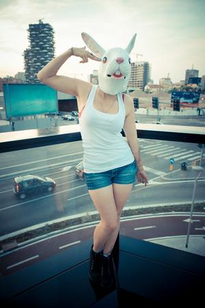 うさぎマスクの街で若い美しい長い巻き毛流行に敏感な女性